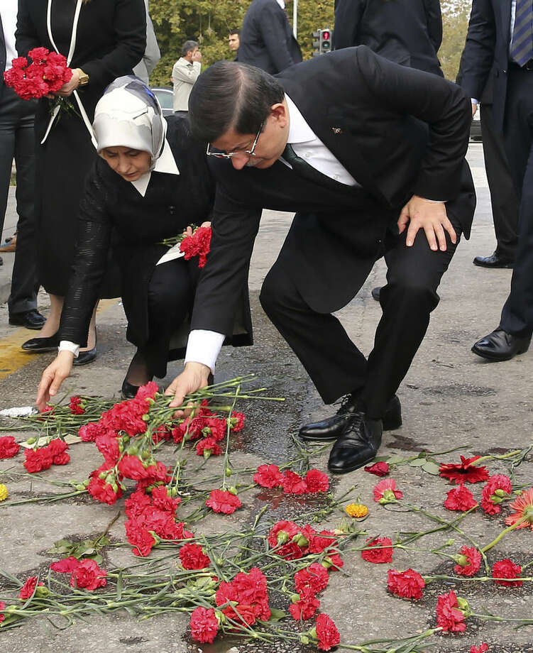 Turkish Prime Minister Ahmet Davutoglu and his wife Sare Davutoglu leave carnations at the site of an explosion in Ankara, Turkey, Tuesday, Oct. 13, 2015. Authorities in Istanbul banned a protest rally and march by the same trade union and civic society groups who lost friends and colleagues in Turkey's bloodiest terror attack. Dogan news agency video footage on Tuesday showed police pushing back dozens of demonstrators trying to reach the rally to commemorate the 97 victims of the twin suicide bombings. Some demonstrators were detained. (Mustafa Aktas/Prime Ministry Press Service via AP, Pool)
