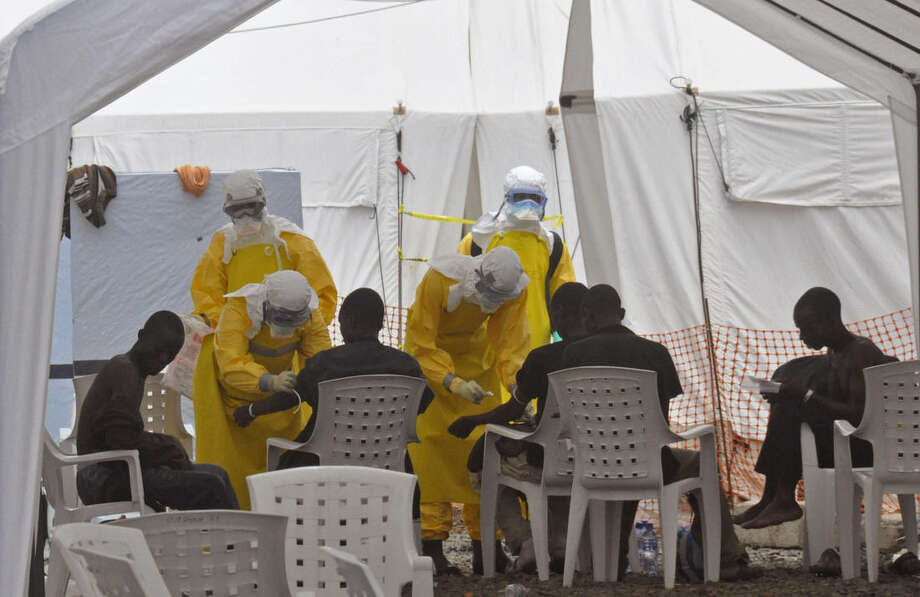 Health workers, attend to patients that contracted the Ebola virus, at a clinic in Monrovia, Liberia, Monday, Sept. 8, 2014. Border closures, flight bans and mass quarantines are creating a sense of siege in the West African countries affected by Ebola, officials at an emergency African Union meeting said Monday, as Senegal agreed to allow humanitarian aid pass through its closed borders. (AP Photo/Abbas Dulleh)