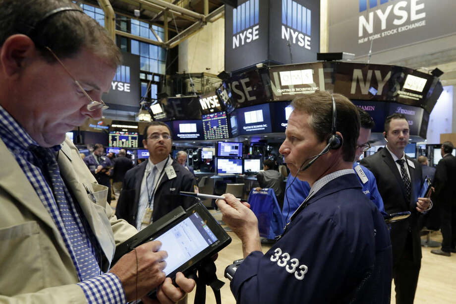 Traders work on the floor of the New York Stock Exchange, Monday, Oct. 12, 2015. Stocks are little changed in early trading as traders look ahead to the start of corporate earnings season. (AP Photo/Richard Drew)