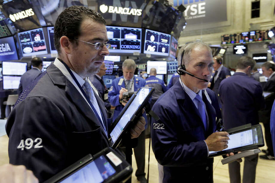 Timothy Nick, right, works with fellow traders on the floor of the New York Stock Exchange, Monday, Oct. 12, 2015. Stocks are little changed in early trading as traders look ahead to the start of corporate earnings season. (AP Photo/Richard Drew)