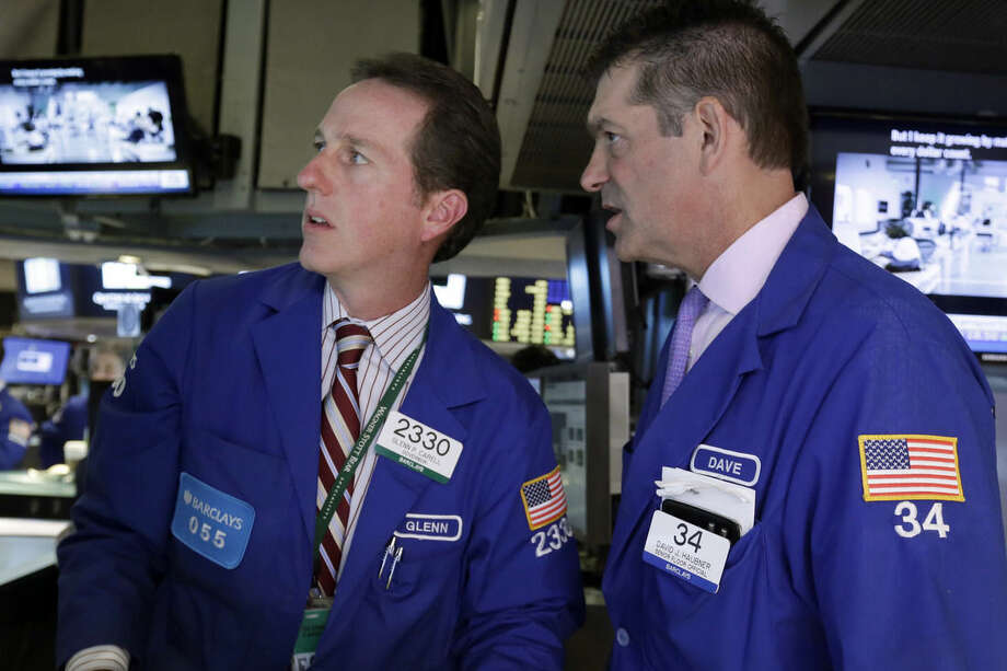 Specialists Glenn Carell, left, and David Haubner work on the floor of the New York Stock Exchange, Monday, Oct. 12, 2015. Stocks are little changed in early trading as traders look ahead to the start of corporate earnings season. (AP Photo/Richard Drew)