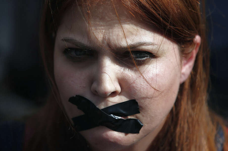 A woman places a bandage other mouth as she protests Saturday's explosions in Ankara, Turkey, Tuesday, Oct. 13, 2015. Authorities in Istanbul banned a protest rally and march by the same trade union and civic society groups who lost friends and colleagues in Turkey's bloodiest terror attack. Dogan news agency video footage on Tuesday showed police pushing back dozens of demonstrators trying to reach the rally to commemorate the 97 victims of the twin suicide bombings. Some demonstrators were detained.(AP Photo/Emrah Gurel)
