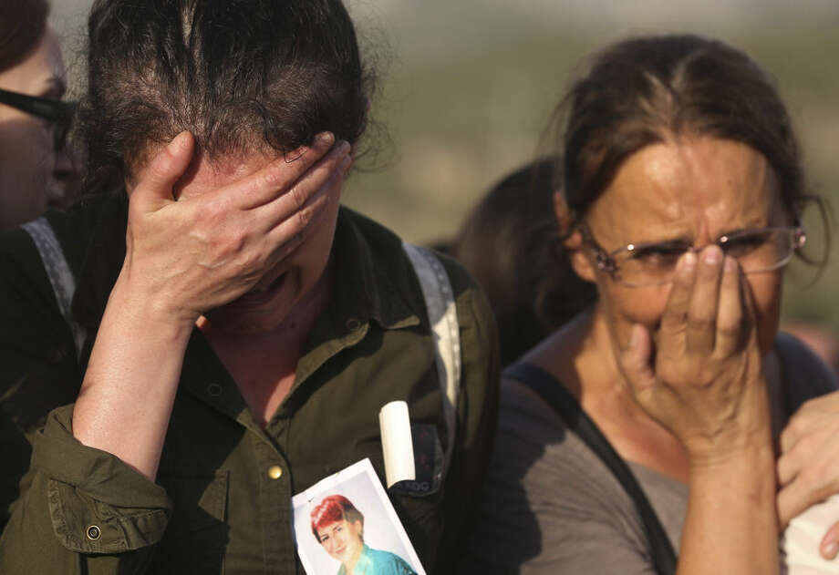 Mourners, one wearing a picture of Ayse Deniz, one of the victims of Saturday's Ankara bombing attacks, cry during a funeral in Izmir, Turkey, Monday, Oct. 12, 2015. Turkish investigators are close to identifying one of the suicide bombers in Turkey's deadliest attacks in years, Prime Minister Ahmet Davutoglu said Monday. (AP Photo/Emre Tazegul)