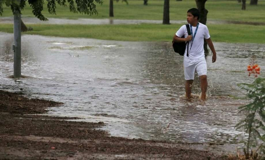 A student tries to walk along a flooded sidewalk to a non-flooded street so he can be picked up by his parents after schools were closed as heavy rains pour down causing severe flooding Monday, Sept. 8, 2014, in Phoenix. Storms that flooded several Phoenix-area freeways and numerous local streets during the Monday morning commute set an all-time record for rainfall in Phoenix in a single day. (AP Photo/Ross D. Franklin)
