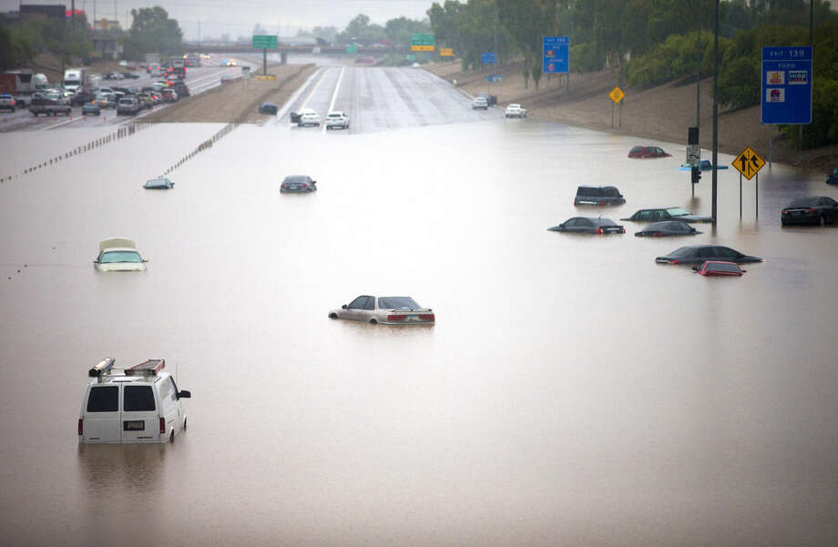 Cars are stuck in flood waters on I-10 east at 43rd Ave. after heavy storms pounded the Phoenix area early Monday, flooding major freeways, prompting several water rescues and setting an all-time single-day record for rainfall in the desert city. (AP Photo/The Arizona Republic, Michael Chow) MARICOPA COUNTY OUT - NO MAGS- NO SALES - MANDATORY CREDIT