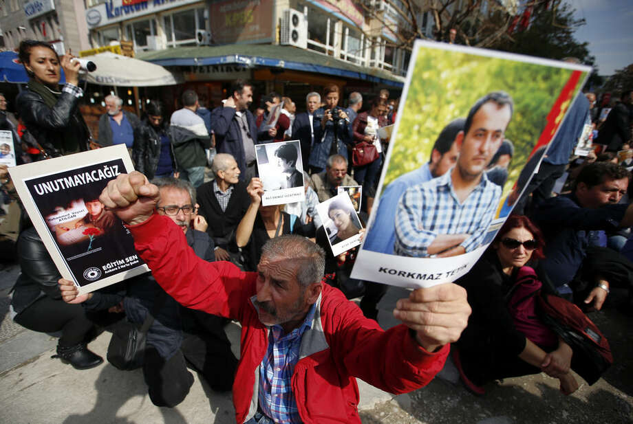 People hold images of victims as they protest Saturday's explosions in Ankara, Turkey, Tuesday, Oct. 13, 2015. Authorities in Istanbul banned a protest rally and march by the same trade union and civic society groups who lost friends and colleagues in Turkey's bloodiest terror attack. Dogan news agency video footage on Tuesday showed police pushing back dozens of demonstrators trying to reach the rally to commemorate the 97 victims of the twin suicide bombings. Some demonstrators were detained.(AP Photo/Emrah Gurel)