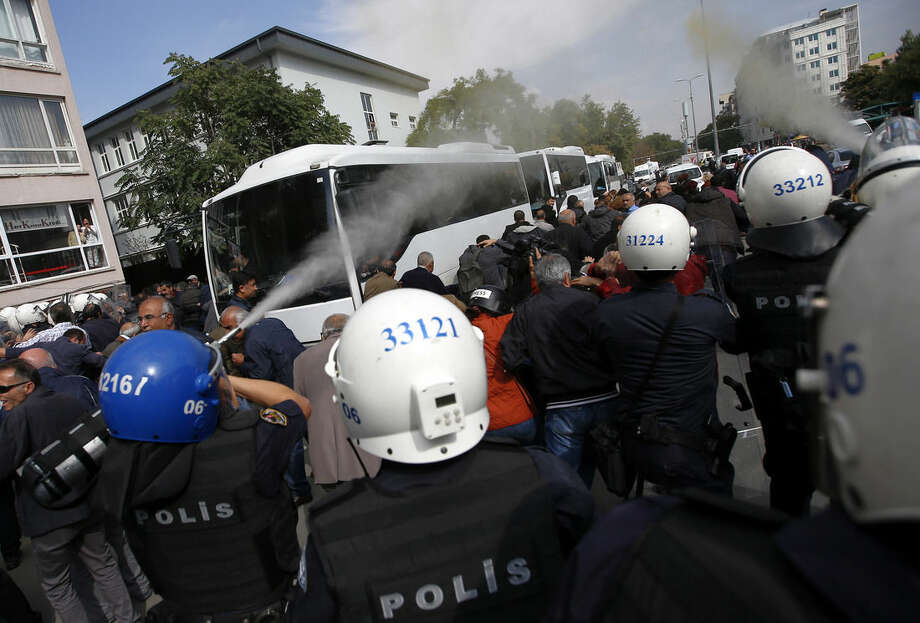 Police use teargas to disperse people who were protesting Saturday's explosions in Ankara, Turkey, Tuesday, Oct. 13, 2015. Authorities in Istanbul banned a protest rally and march by the same trade union and civic society groups who lost friends and colleagues in Turkey's bloodiest terror attack. Dogan news agency video footage on Tuesday showed police pushing back dozens of demonstrators trying to reach the rally to commemorate the 97 victims of the twin suicide bombings. Some demonstrators were detained.(AP Photo/Emrah Gurel)