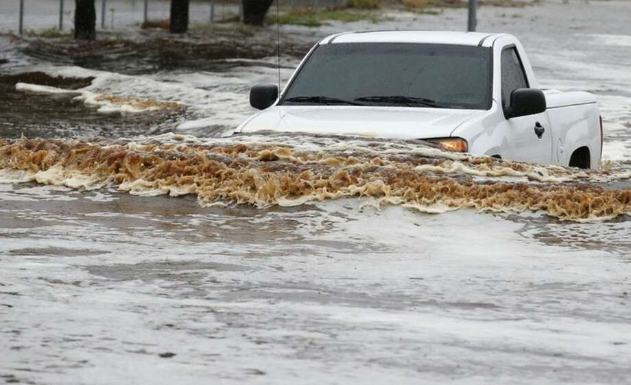 A pick-up truck driver tries to navigate a severely flooded street as heavy rains pour down Monday, Sept. 8, 2014, in Phoenix. Storms that flooded several Phoenix-area freeways and numerous local streets during the Monday morning commute set an all-time record for rainfall in Phoenix in a single day. (AP Photo/Ross D. Franklin)