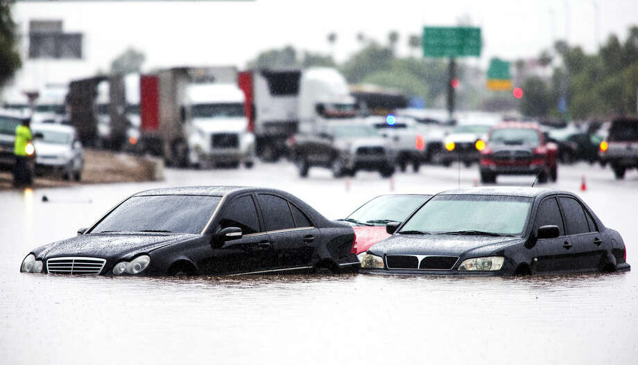 Traffic is stopped in the eastbound lanes of I-10 and cars are underwater at 43rd Ave. and I-10 in the westbound lanes in Phoenix, Monday, Sept. 8, 2014 after record-setting rainfall caused massive flooding throughout the Valley. More than 20 cars were stranded when fast rising water flooded the underpass. (AP Photo/The Arizona Republic, Tom Tingle) ***MARICOPA COUNTY OUT - NO MAGS- NO SALES - MANDATORY CREDIT***