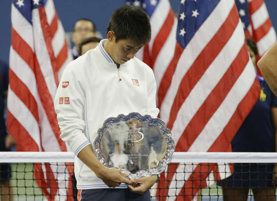 Kei Nishikori, of Japan, stands with the second place trophy after losing Marin Cilic, of Croatia, in the championship match of the 2014 U.S. Open tennis tournament, Monday, Sept. 8, 2014, in New York. (AP Photo/Darron Cummings)