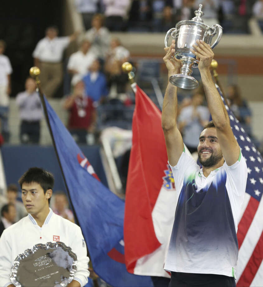 Marin Cilic, of Croatia, right, holds up the championship trophy after defeating Kei Nishikori, of Japan, left, in the championship match of the 2014 U.S. Open tennis tournament, Monday, Sept. 8, 2014, in New York. (AP Photo/Darron Cummings)