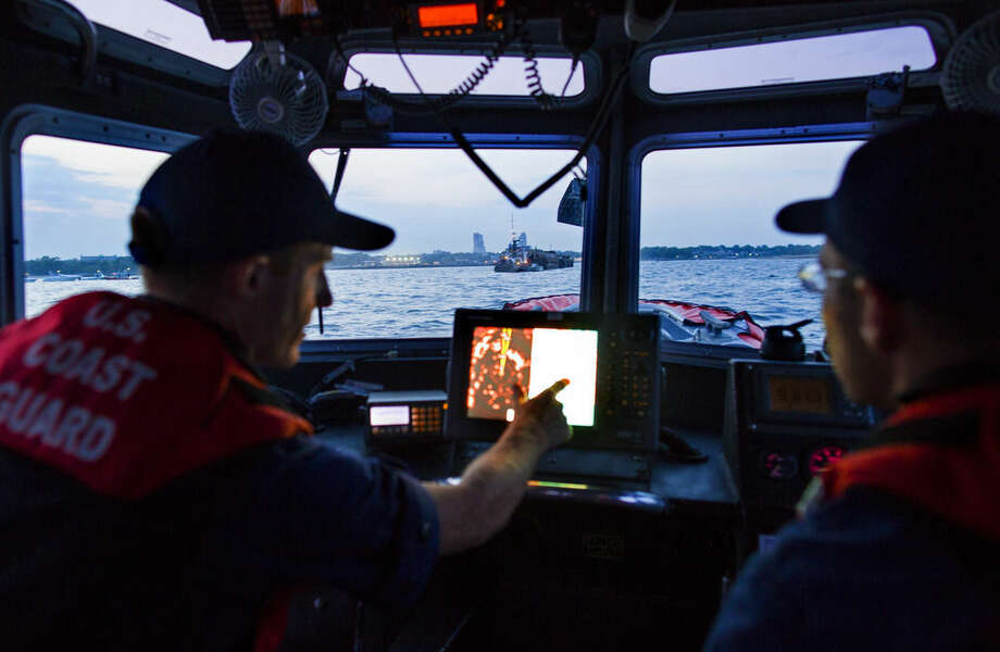 In this photo taken July 12, 2014, U.S. Coast Guard 2nd Class Petty Officer Geoffrey Burns, left, and 3rd Class Petty Officer John Huber, at the wheel of a response boat, patrol near a barge, seen in front window, that would soon be the water base of a fireworks display off Glen Island in western Long Island Sound near New Rochelle, N.Y. A wedding celebrated on Glen Island featured fireworks, and the Coast Guard engaged in keeping a safe zone for boaters around the pyrotechnics. (AP Photo/Craig Ruttle)