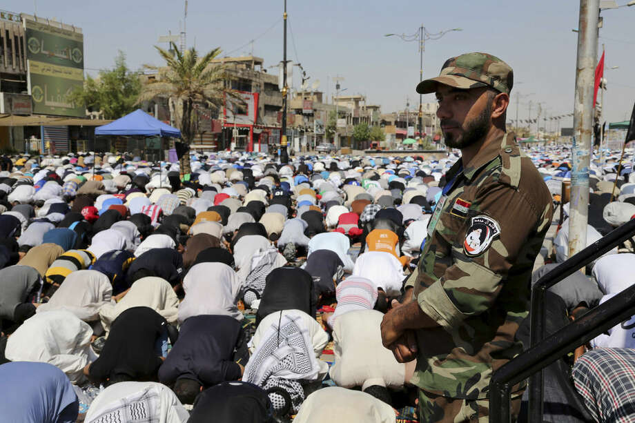 A Shiite fighter stands guard over followers of Shiite cleric Muqtada al-Sadr attending open-air Friday prayers in the Shiite stronghold of Sadr City, Baghdad, Iraq, Friday, Sept. 5, 2014. (AP Photo/Karim Kadim)