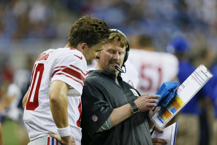 New York Giants quarterback Eli Manning talks with offensive coordinator Ben Mcadoo during the second quarter of an NFL football game against the Detroit Lions in Detroit, Monday, Sept. 8, 2014. (AP Photo/Paul Sancya)