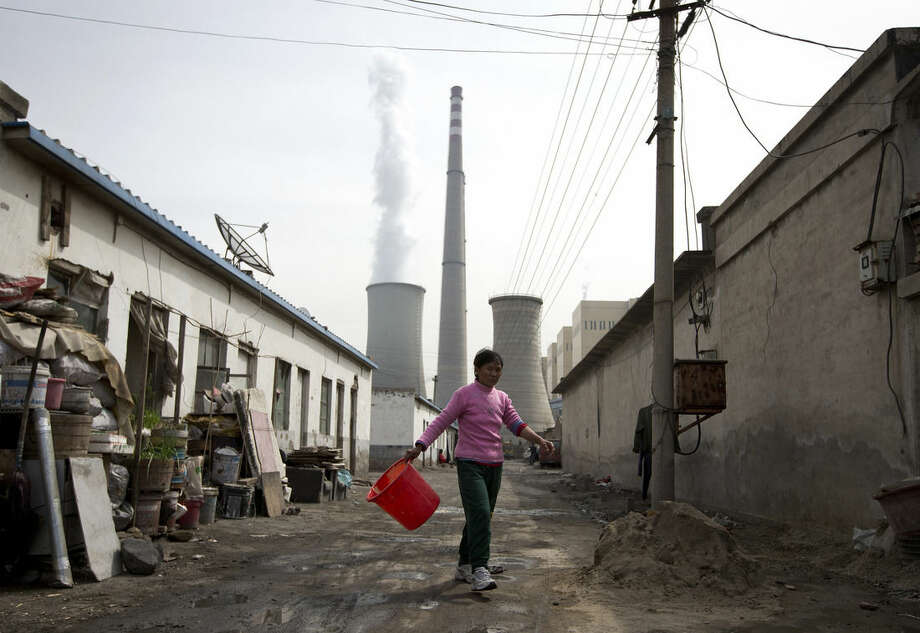 FILE - In this April 12, 2013 file photo, a woman walks through a neighborhood near a coal-fired power plant in Beijing. Carbon dioxide levels in the atmosphere reached a record high in 2013 as increasing levels of man-made pollution transform the planet, the U.N. weather agency said Tuesday, Sept. 9, 2014. (AP Photo/Andy Wong, File)