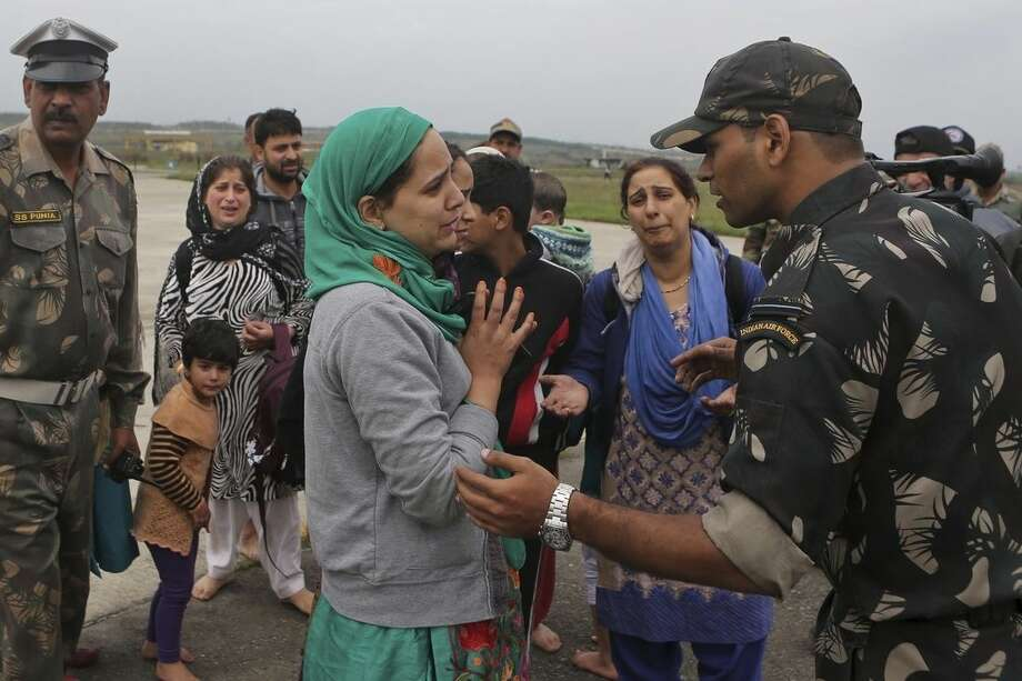 A Kashmiri flood victim, center, pleads to an Indian army officer to rescue her family members after she was airlifted by the army from her flooded neighborhood to the Indian Air Force base in Srinagar, India, Monday, Sept. 8, 2014. Six days of rains in Indian Kashmir have left more than 120 people dead in the region's worst flooding in more than five decades, submerging hundreds of villages and triggering landslides, officials said. (AP Photo/Dar Yasin)