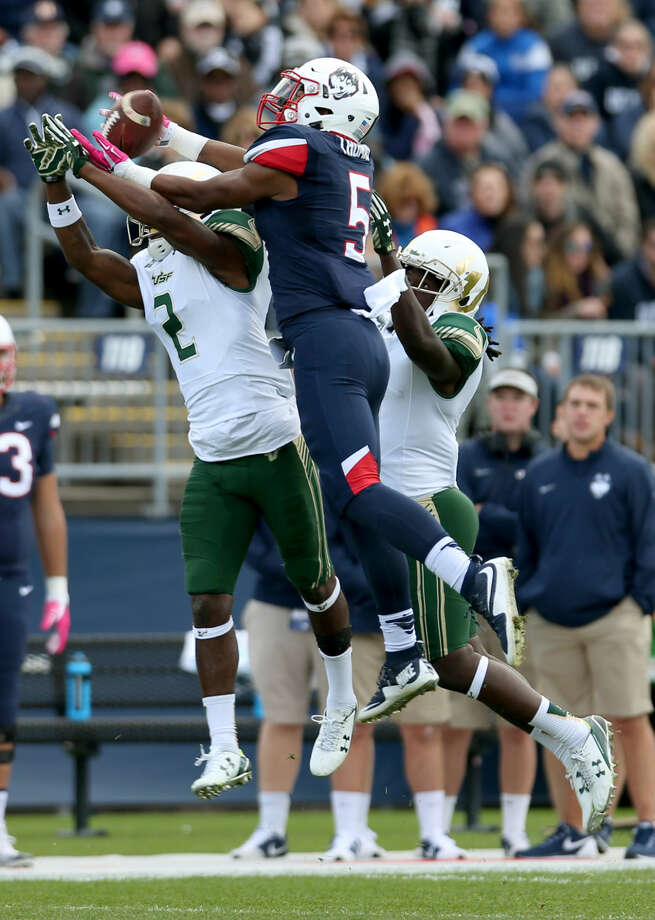 Connecticut wide receiver Noel Thomas (5) hauls in a pass over South Florida defensive back Jamie Byrd (2) during the first half of an NCAA college football game, Saturday, Oct. 17, 2015, in East Hartford, Conn. (AP Photo/Mary Schwalm)