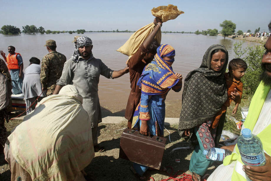 Pakistani villagers who have been effected by the flood arrive to find safe shelters in Pindi Bhatian, 105 kilometers (65 miles) northeast of Lahore, Pakistan, Monday, Sept. 8, 2014. Army and air force troops on Monday worked to rescue thousands of people stranded in Indian-controlled Kashmir and northern and eastern Pakistan, where flooding and landslides have caused hundreds of deaths. (AP Photo/K.M. Chaudary)