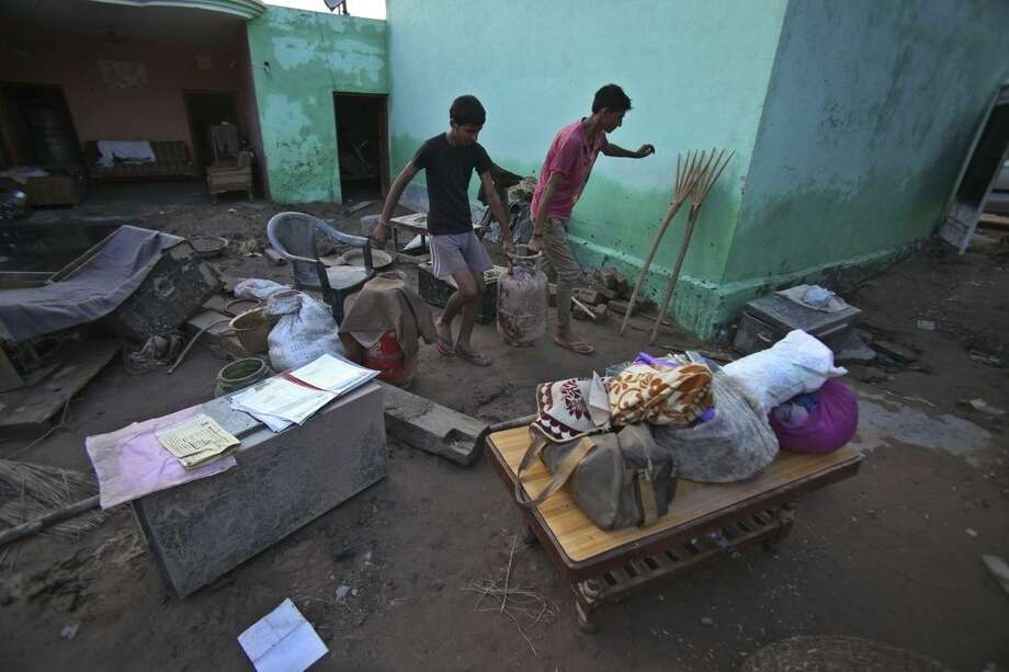 Flood affected Indian villagers salvage their belongings on the outskirts of Jammu, India, Monday, Sept. 8, 2014. Six days of rains in Indian Kashmir have left more than 120 people dead in the region's worst flooding in more than five decades, submerging hundreds of villages and triggering landslides, officials said. (AP Photo/Channi Anand)