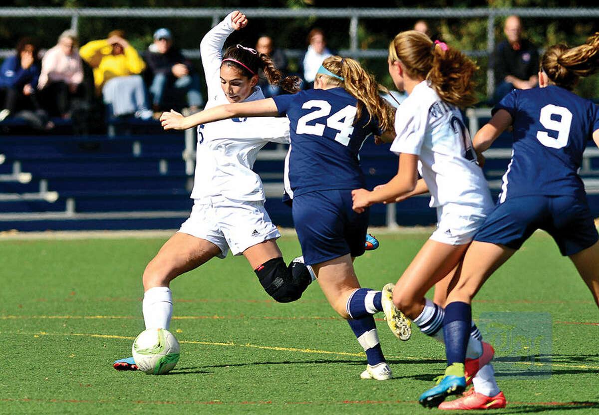Hour photo / Erik Trautmann Wilton High School's #5 Lindsay Groves evades #24 Erin Lynch of Staplesduring their girls soccer game in Wilton Saturday.