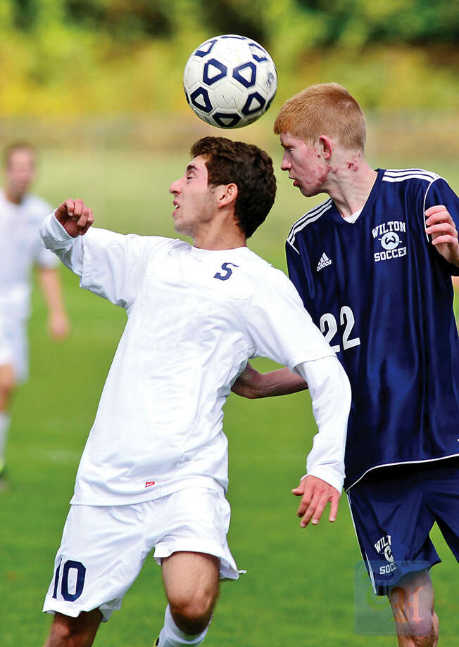 Hour photo / Erik TrautmannStaples' Daniel Perez Elorza battles Wilton's Patrick Prinner for the ball on Saturday.