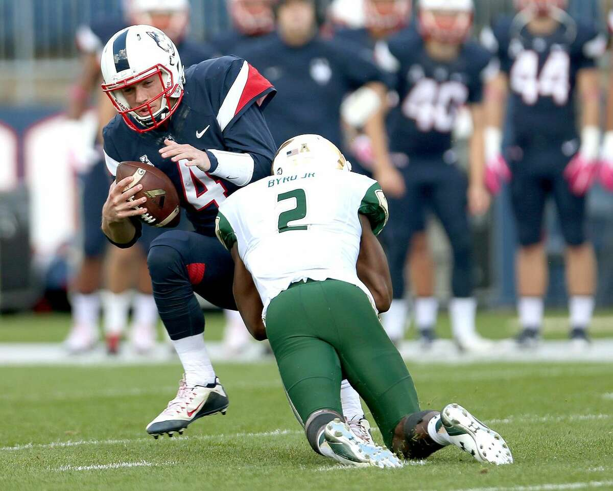 Connecticut quarterback Bryant Shirreffs (4) is sacked by South Florida defensive back Jamie Byrd (2) during the first half of an NCAA college football game, Saturday, Oct. 17, 2015, in East Hartford, Conn. (AP Photo/Mary Schwalm)