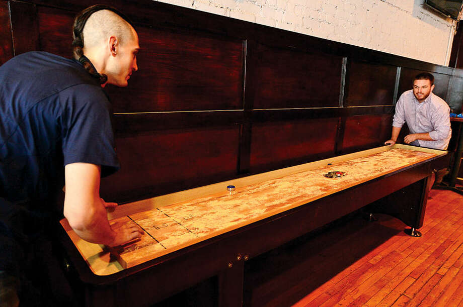 Hour photo / Erik Trautmann Owners, Matt Bacco, Casey Dohme play shuffleboard wwhich will be a featured game at the new sports bar, Blind Rhino, on North Main St in SoNo next Friday