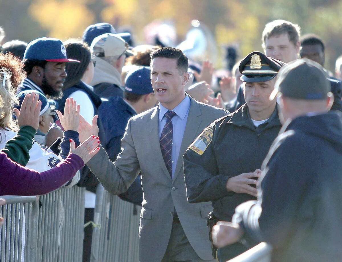 Connecticut head coach Bob Diaco high-fives fans as he leads his team to the stadium before the start of an NCAA college football game against South Florida, Saturday, Oct. 17, 2015, in East Hartford, Conn. (AP Photo/Mary Schwalm)