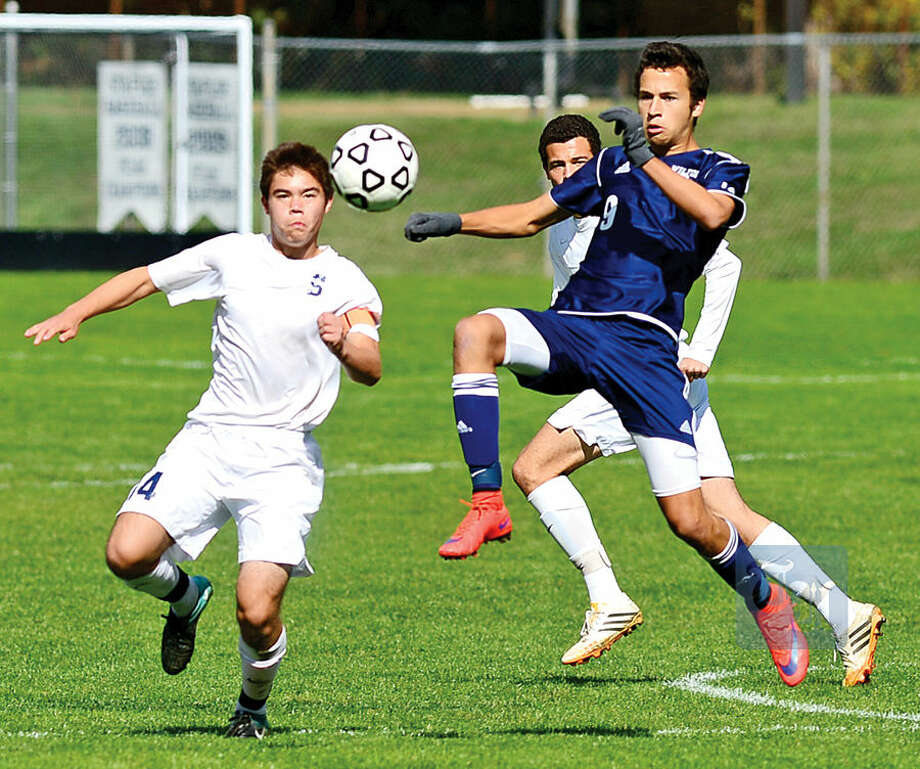 Hour photo / Erik Trautmann Wilton High School's #9 Harry Allers gets the ball away from Staples' #14 Kenji Goto in their boys soccer game Saturday in Westport.