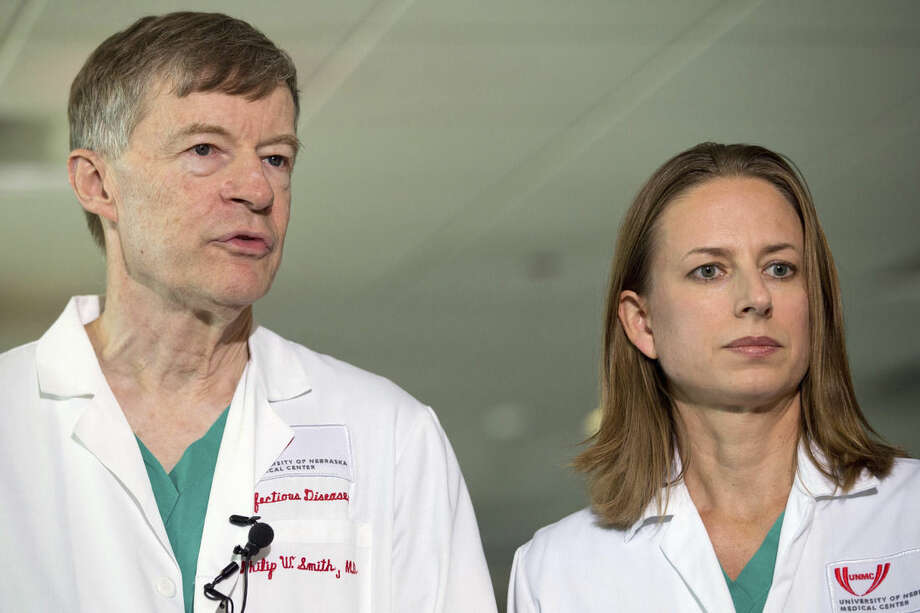 Dr. Philip W. Smith, left, and Dr. Angela Hewlett speak during a news conference about the condition of Dr. Rick Sacra, Sunday, Sept. 7, 2014, in Omaha Neb. Sacra who became infected with Ebola arrived at the Nebraska Medical Center on Friday for treatment in the hospital's specialized 10-bed isolation unit. The 51-year-old Sacra is the third American aid worker to be sickened with the Ebola virus. (AP Photo/The World-Herald, Sarah Hoffman) MAGS OUT; ALL NEBRASKA LOCAL BROADCAST TELEVISION OUT