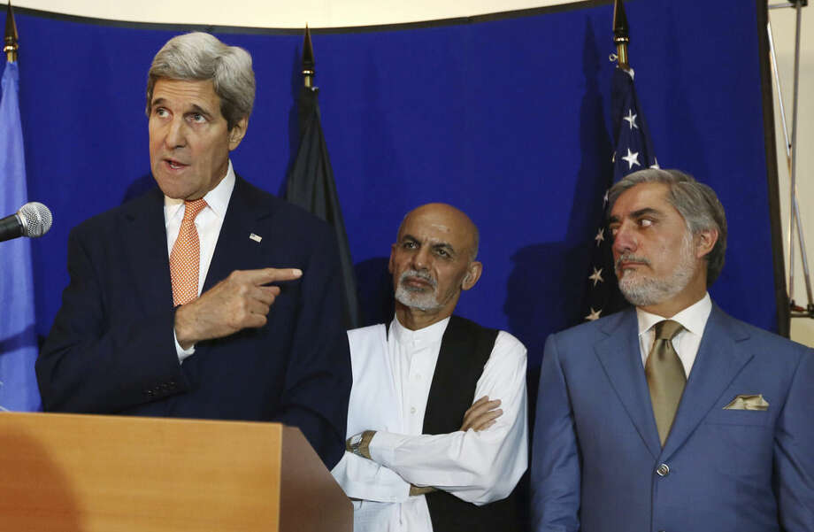 "FILE - In this Friday, Aug. 8, 2014 file photo, U.S. Secretary of State John Kerry, left, speaks as Afghan presidential candidates Ashraf Ghani Ahmadzai, center, and Abdullah Abdullah listen during a joint press conference in Kabul, Afghanistan. ""Radicals"" backing Abdullah could foment postelection violence if he isn't given an equitable share of power, his spokesman warned Saturday, Sept. 6, 2014 ahead of a meeting with his rival aimed at resolving a monthslong election dispute. U.S. Secretary of State John Kerry helped broker an agreement this summer under which all 8 million ballots would be recounted, a process which was concluded Friday. (AP Photo/Rahmat Gul, File)"