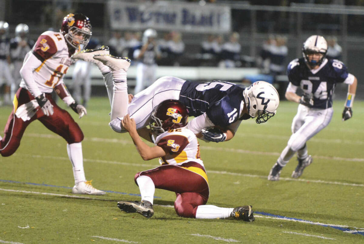 Hour Photo/Alex von Kleydorff Wilton's Jack Dooley is upended by a St. Joseph defender during Friday's FCIAC tilt at Fujitani Field. The Warriors lost to the Cadets 35-0.