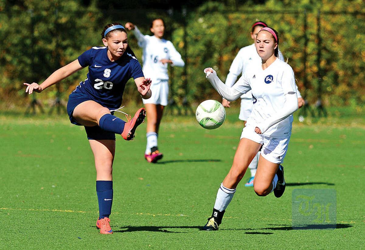 Hour photo / Erik Trautmann Staples High School girls soccer #20 Anne Amacker clears the ball during their game against Wilton Saturday.