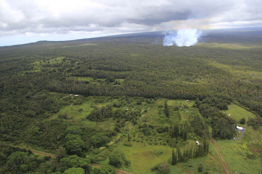 This Monday Sept. 8, 2014, aerial photo provided by the U.S. Geological Survey, shows a smoke plume from the June 27th flow from the Kilauea volcano in Pahoa, Hawaii. Lava from one of the world's most active volcanos has been advancing at a slower pace the past few days and is now moving parallel to a sparsely populated subdivision on Hawaii's Big Island. (AP Photo/U.S. Geological Survey, Tim Orr)