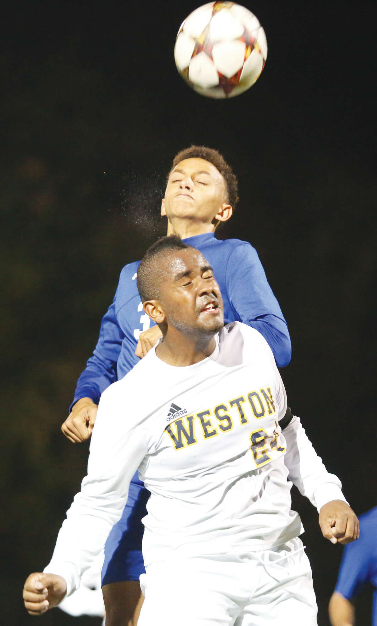 Hour photo/Chris Palermo Weston's Sam Chicha jumps for a header against a Bunnell defenseman Tuesday night.