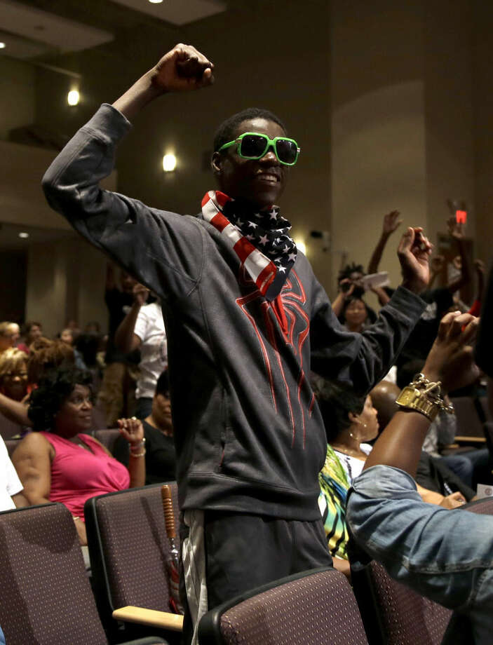Joshua Williams raises his arms during a meeting of the Ferguson City Council Tuesday, Sept. 9, 2014, in Ferguson, Mo. The meeting is the first for the city council since the fatal shooting of Michael Brown by a city police officer. (AP Photo/Jeff Roberson)