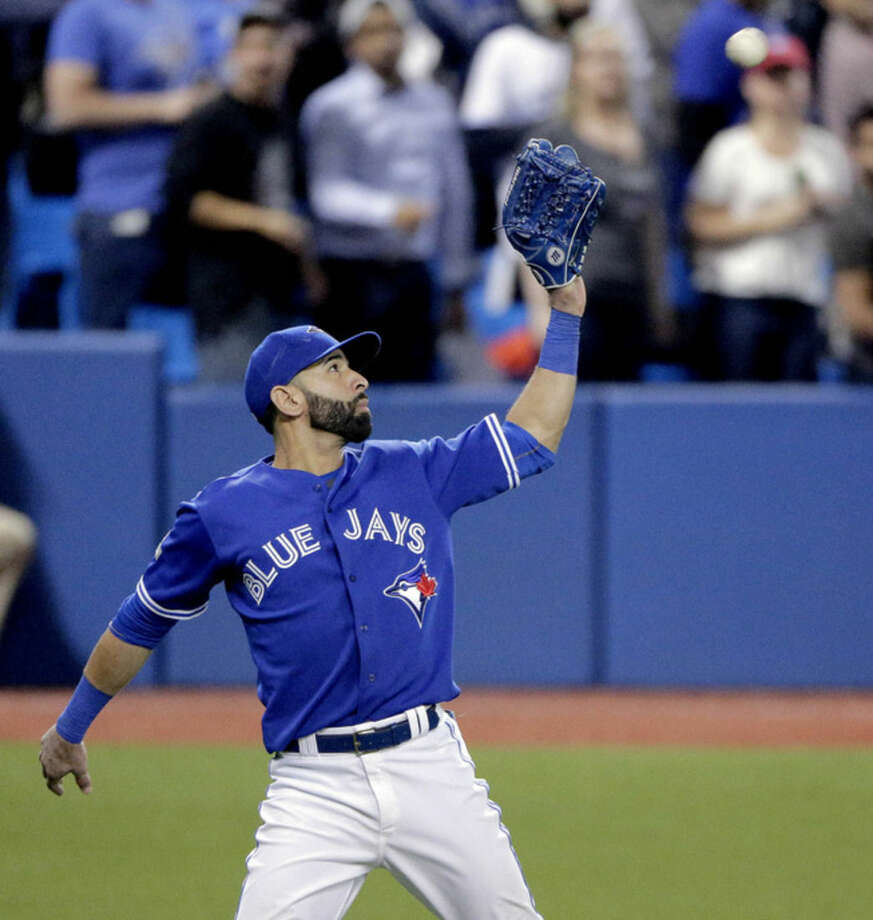 Toronto Blue Jays right fielder Jose Bautista catches a fly ball by Kansas City Royals' Alcides Escobar during the eighth inning in Game 5 of baseball's American League Championship Series on Wednesday, Oct. 21, 2015, in Toronto. (AP Photo/Charlie Riedel)