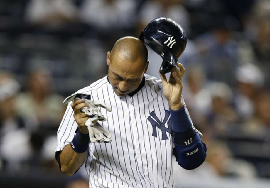New York Yankees' Derek Jeter removes his batting helmet after lining out into an inning-ending double play in the fifth inning of a baseball game against the Tampa Bay Rays at Yankee Stadium in New York, Tuesday, Sept. 9, 2014. (AP Photo/Kathy Willens)