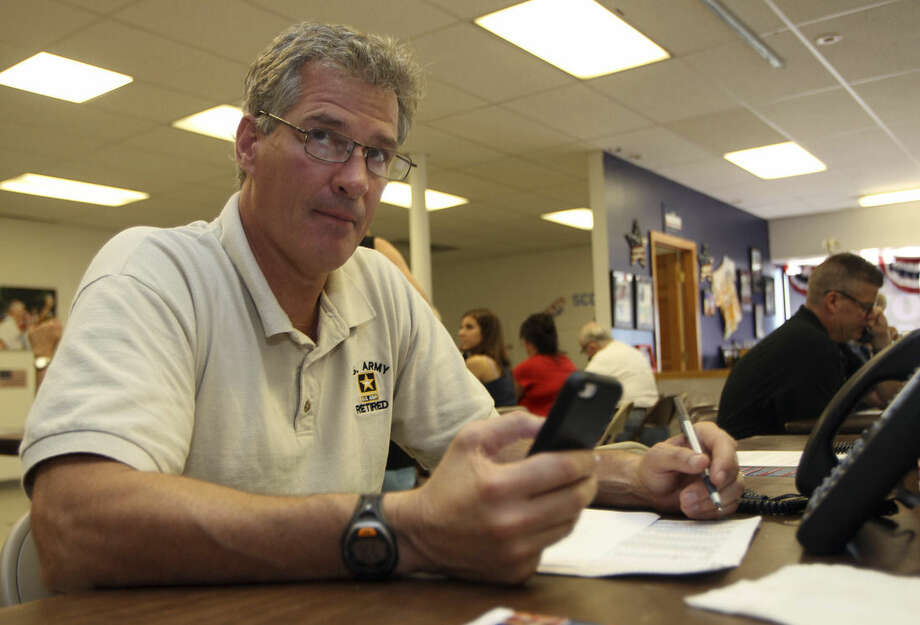 Scott Brown, a former U.S. Senator from Massachusetts, makes phone calls to voters from his headquarters Tuesday Sept. 9, 2014 in Manchester, N.H. Brown moved to New Hampshire and is seeking the Republican party nomination for U.S. Senate hoping to unseat Democrat Jeanne Shaheen. (AP Photo/Jim Cole)