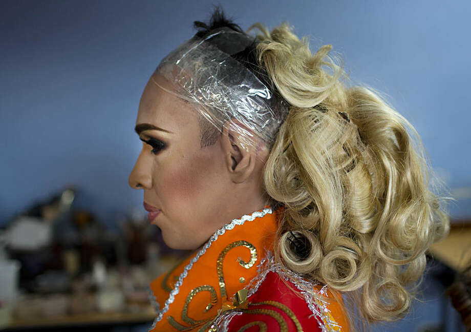 In this Oct. 18, 2015 photo, contestant Eduardo Ramirez, Miss Gay Trujillo, sits backstage with his hair half-finished ahead of the ninth annual Miss Gay Venezuela beauty pageant in Caracas, Venezuela. Contestants spend a lot of money and time searching for products that are hard to come by in Venezuela, due to currency controls and the scarcity of some goods, such as color contact lenses, hair spray, artificial eyelashes and body make-up. (AP Photo/Ariana Cubillos)