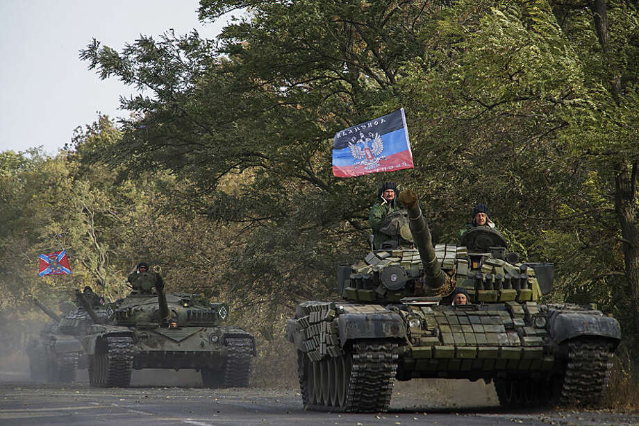 Russia-backed rebel tanks with a flag of the self-proclaimed Donetsk People's Republic, move to storage during the withdrawal of weapons near Novoazovsk, eastern Ukraine, Wednesday, Oct. 21, 2015. Separatists in eastern Ukraine continued their military withdrawal from the Donetsk region. (AP Photo/Max Black)