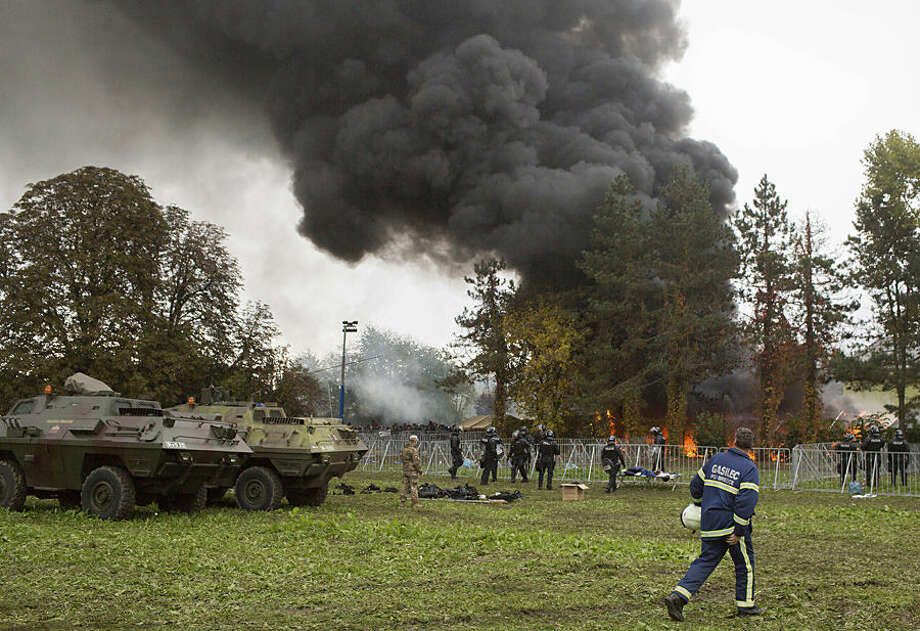 A plume of smoke rises from a camp for migrants near Slovenia's border with Croatia, in Brezice, Slovenia, Wednesday, Oct. 21, 2015. It was not clear what caused the fire that has broken out in the camp which is housing thousands of migrants, including women and children. (AP Photo/Matej Leskovsek)