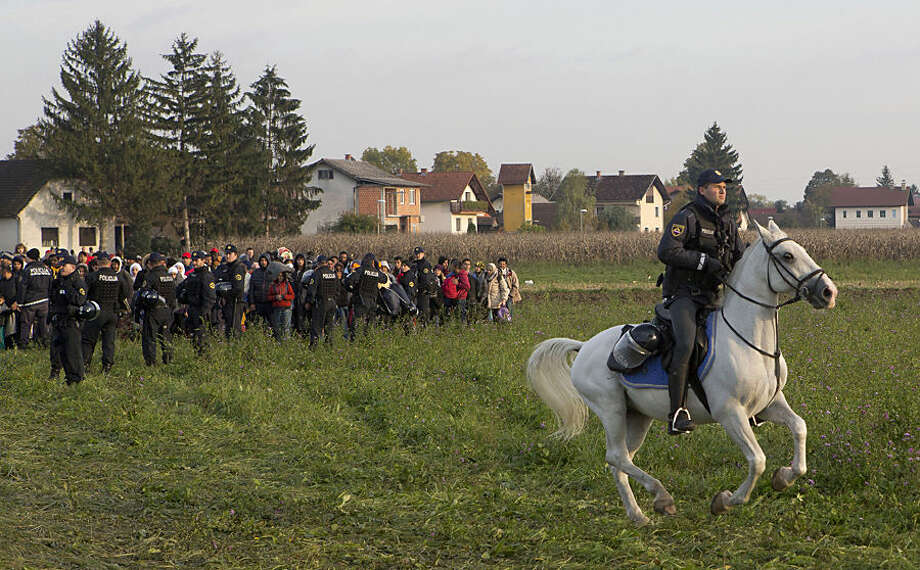 A policeman rides on his horse as a group of migrants is stopped by Slovenian police after crossing from Croatia, in Dobova, Slovenia, , near a border crossing between Croatia and Slovenia, Wednesday, Oct. 21, 2015. A massive influx of migrants has increased tensions in the Balkans, which saw years of war in 1990s. Tense Balkan neighbors have been accusing each other of mishandling the flow of hundreds of thousands of people through the region toward Western Europe. (AP Photo/Darko Bandic)