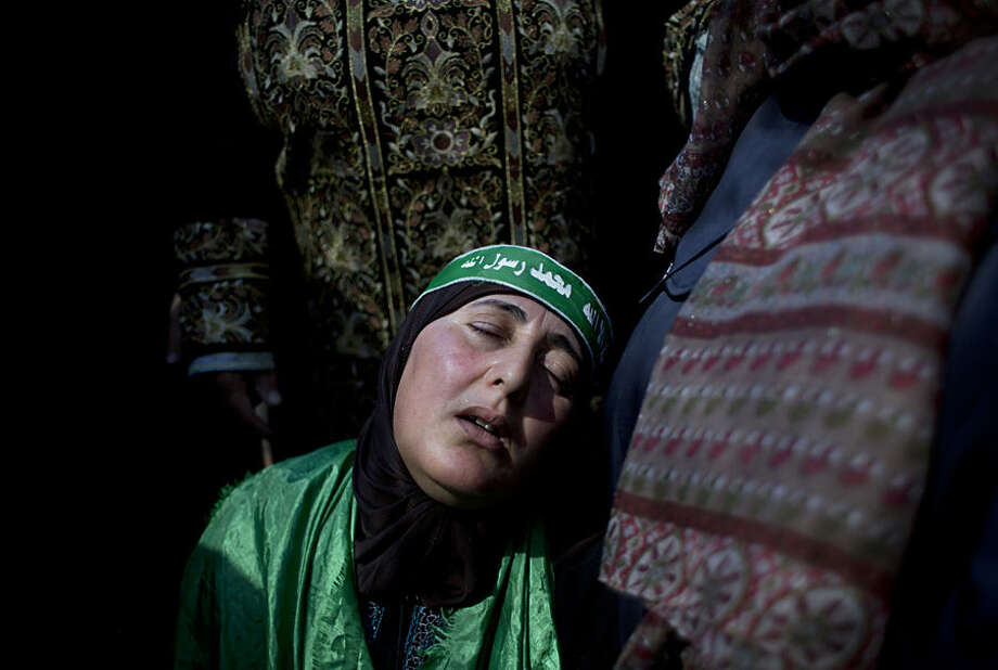 Palestinian Hureyah Masalmeh, 41, the mother of slain of Udai Masalmeh, 24, mourns during her son's funeral at the family house in the West Bank village of Beit Awa, Hebron, Wednesday, Oct. 21, 2015. The 24 year old Palestinian was fatally shot near the village of Beit Awa after lightly injuring an Israeli army officer with a knife, according to a statement from the military. The incident reportedly occurred during Palestinian protests the army described as violent. (AP Photo/Nasser Nasser)