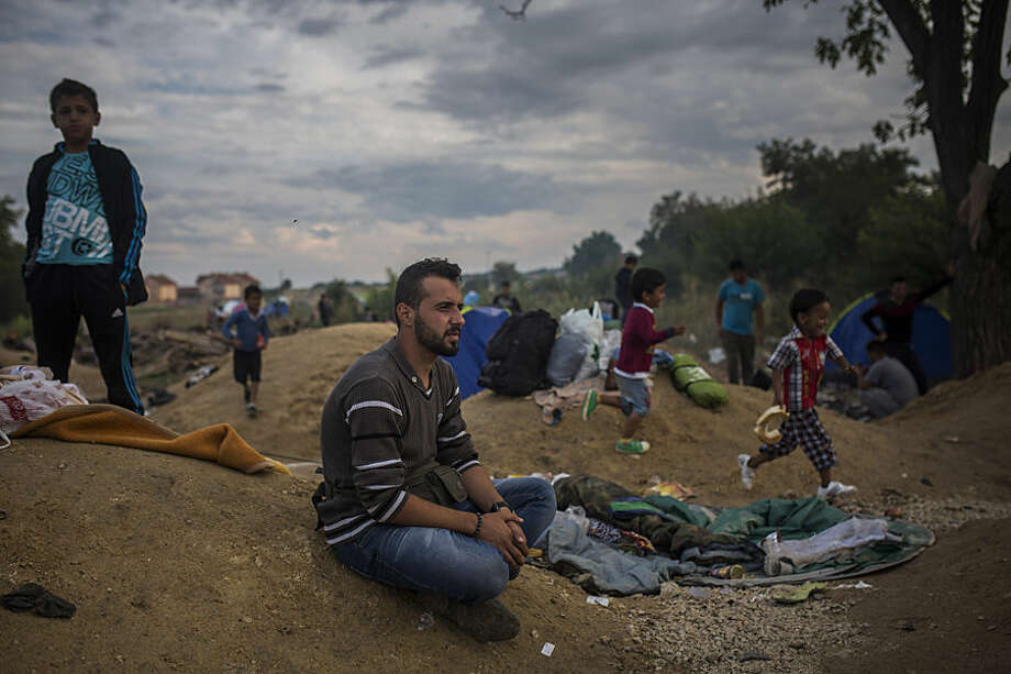 After crossing through Macedonia and into Serbia, Mohammed al-Haj ended up in another bottleneck-turned-madhouse, the town of Presevo. In this Friday, Sept. 11, 2015 photo, Mohammed sits in a lot in the city as refugee children play around him and other families settle in. The city was teeming with migrants trying to get Serbian registration papers required before they could continue on to Hungary, a process that could take hours or days. (AP Photo/Santi Palacios)