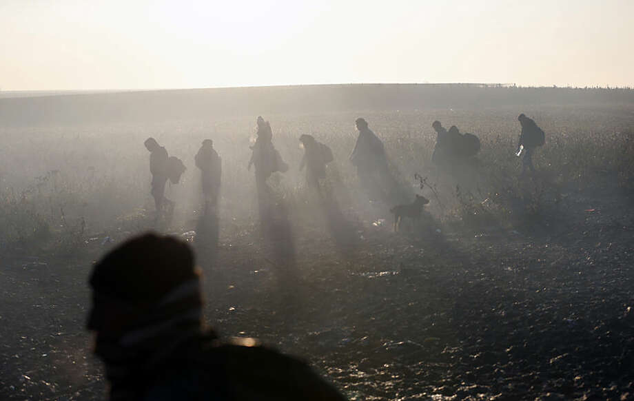 Migrants walk in the field in the morning mist near a borderline between Serbia and Croatia, near the village of Berkasovo, Serbia, Wednesday, Oct. 21, 2015. Croatia, which has erected relatively few shelters along its borders with Serbia and Slovenia, directed thousands into special trains and bus convoys Tuesday to Slovenia in an apparently concerted effort to clear a backlog built up since Saturday, when Hungary closed its borders with Croatia. (AP Photo/Darko Vojinovic)