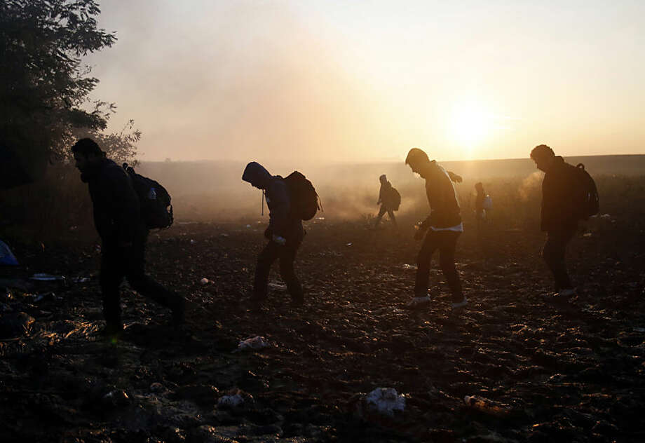 People walk in the field near a borderline between Serbia and Croatia, near the village of Berkasovo, Serbia, Wednesday, Oct. 21, 2015. Croatia, which has erected relatively few shelters along its borders with Serbia and Slovenia, directed thousands into special trains and bus convoys Tuesday to Slovenia in an apparently concerted effort to clear a backlog built up since Saturday, when Hungary closed its borders with Croatia. (AP Photo/Darko Vojinovic)