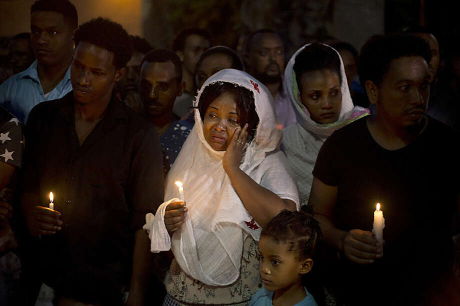 Eritrean migrants hold candles during a memorial gathering for Habtom Zarhum in Tel Aviv, Israel, Wednesday, Oct. 21, 2015. Zarhum died of his wounds after an Israeli security guard fired at him and later was beaten by a mob that mistakenly believed he was a Palestinian attacker during a shooting in the southern city of Beersheba on Sunday. Israeli security officials said a 21-year-old Arab Israeli carried out the attack, killing an Israeli soldier and wounding 10 people. (AP Photo/Ariel Schalit)