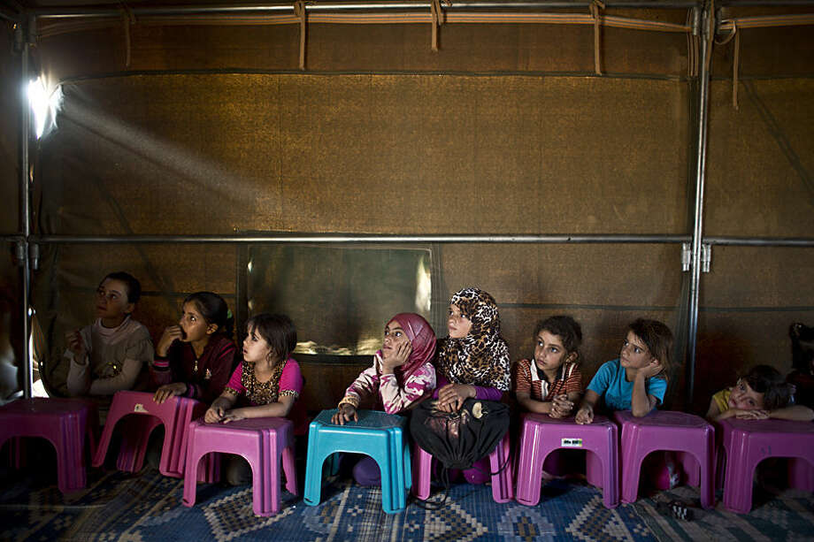 Syrian refugee children attend a class at a makeshift school set up in a tent at an informal tented settlement near the Syrian border on the outskirts of Mafraq, Jordan, Wednesday, Oct. 21, 2015. (AP Photo/Muhammed Muheisen)