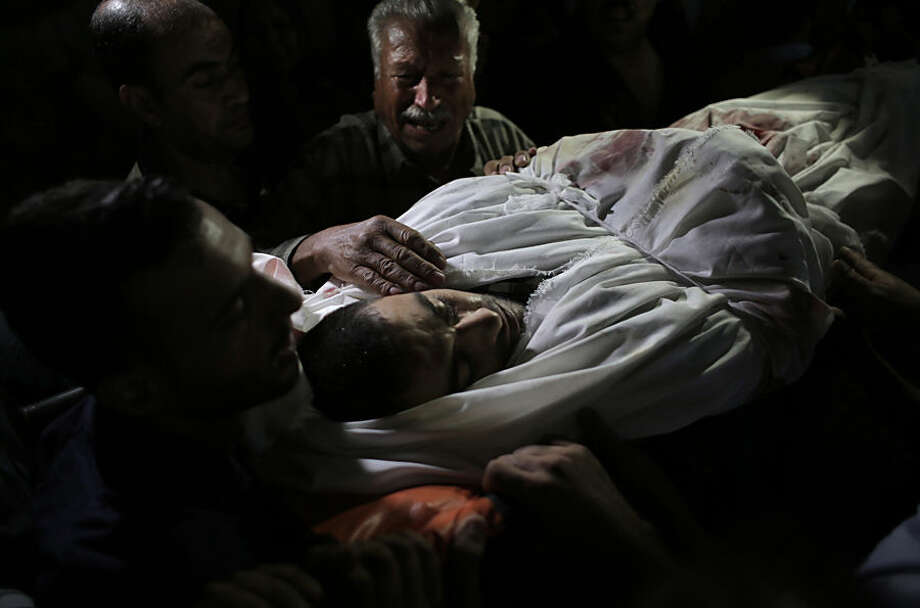 A Palestinian relative mourns over the body of Ahmed Al-Serhi, 27, who was killed during clashes with Israeli troops near the Israeli border with Gaza, during his funeral at the family house in Deir el-Balah, in the central Gaza Strip, Wednesday, Oct. 21, 2015. (AP Photo/ Khalil Hamra)